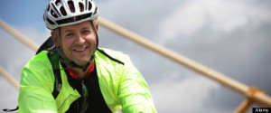 A happy man in cycling outfit wearing a safety jacket and helmet cycling.