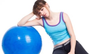 Young woman lying down on a blue exercise ball looking sad and tired