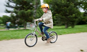 A young girl rides one of the P'tit Velib bicycles